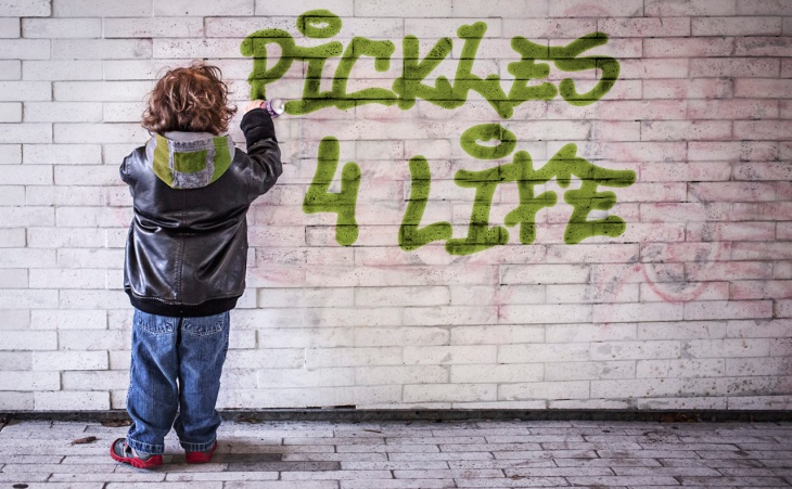 Kids spray painting graffiti of Pickles 4 Life on a brick wall.